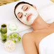 Woman at spa salon with cosmetic mask on face .