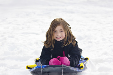 Cute Little Girl going snow sledding down a hill