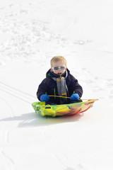 Young Boy snow sledding down a hill