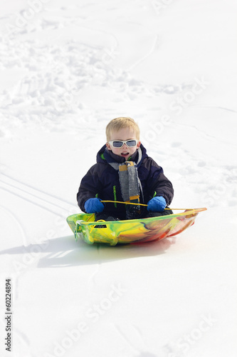 Young Boy snow sledding down a hill