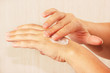 Female hands using skin cream close up