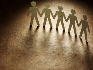 Group of paper people holding hands.