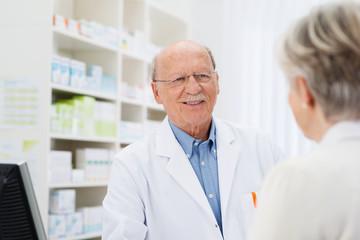 freundlicher älterer apotheker im kundengespräch