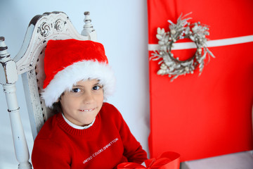 Cute boy with Santa's hat and Christmas wreath
