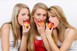 three women biting an apple
