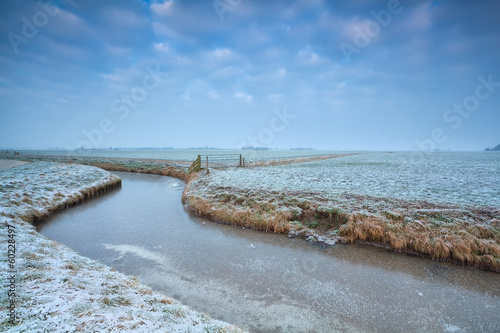 frozen canal on Dutch farmland