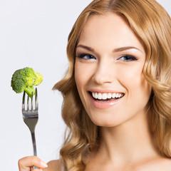 Woman eating broccoli, over gray