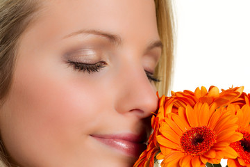 young woman sniffs a gerbera