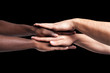 Multiracial hands together forming a pile over dark background