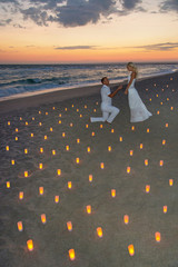 couple at sea beach in candles against sunset