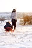 Mother pulling a toboggan with her child in snow