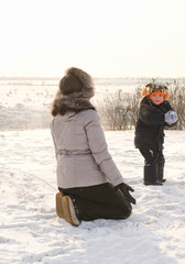 Small boy throwing a snowball at his mother