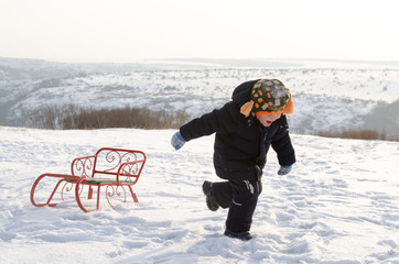 Little boy running through snow with a sled