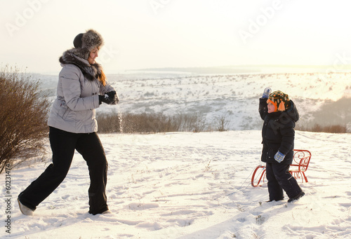 Mother playing with her son in the snow