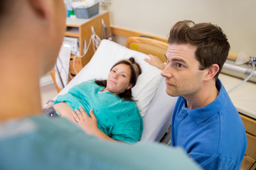 Man And Pregnant Woman Listening To Nurse In Hospital