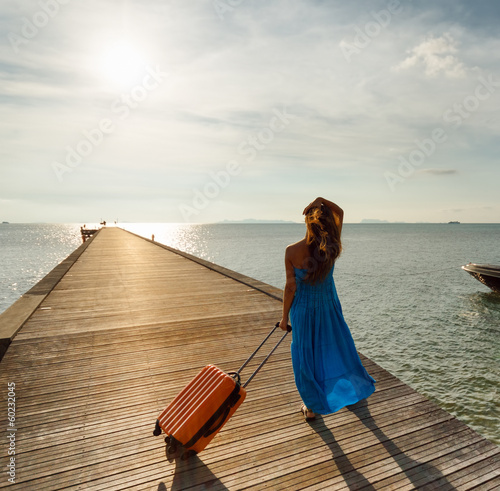 Young woman with suitcase on the pier