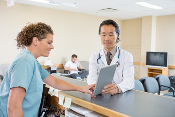 Doctor And Nurse Using Digital Tablet At Hospital Reception