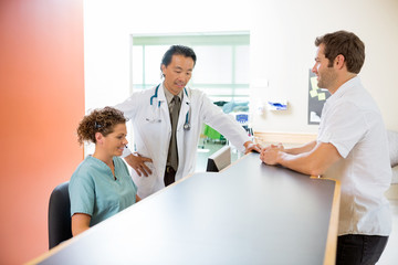 Medical Team Working On Computer While Man Standing At Reception