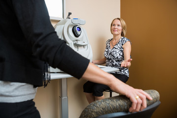 Optician Asking Patient To Sit In Store