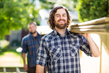 Happy Carpenter With Coworker Carrying Planks Outdoors