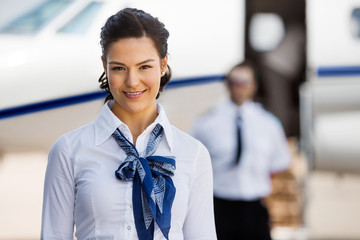 Pretty Stewardesses Smiling With Pilot And Private Jet In Backgr