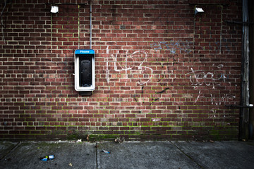 Grungy urban  wall with an old payphone on it © littleny