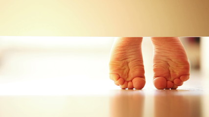 Gently child's feet on the laminate: unusual UNDERbed view