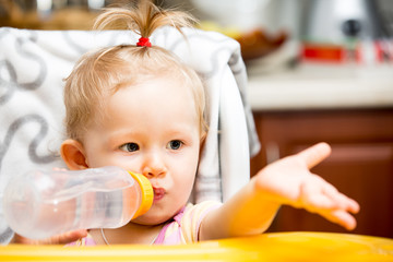 Child girl with bottle with infant formula on kitchen.