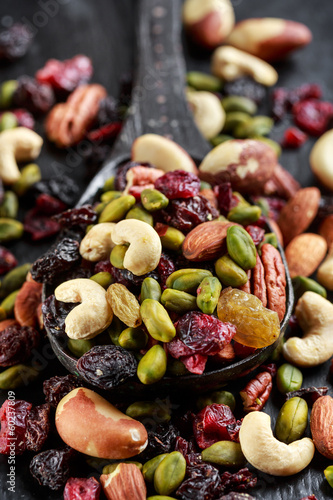 Nuts and dried fruits mix on wooden spoon