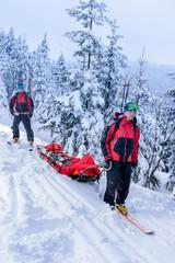 Ski patrol transporting injured skier snow forest