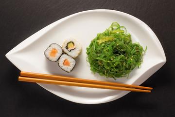 Algensalat mit Maki Sushi und stäbchen