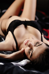 Sexy sensual brunette lying in bed