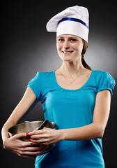Cheerful woman chef wearing hat and holding a po