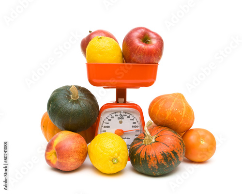 fruits, vegetables and kitchen scale on white background