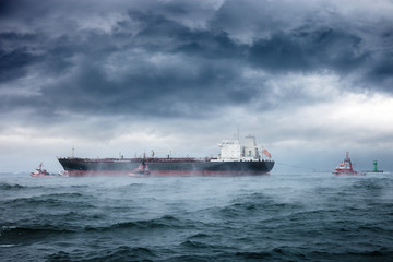 A tanker and tugboats on sea during a violent blizzard.
