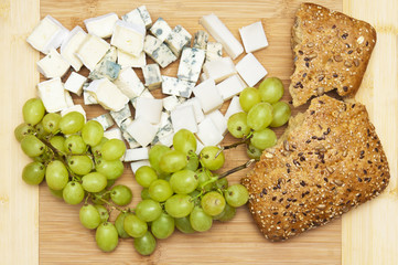 Wooden board with grape, cheese and bread