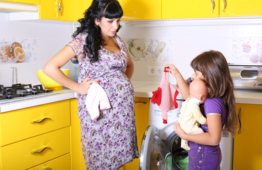 pregnant woman with her little daughter beside washing machine