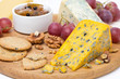 assorted cheeses, grapes, crackers, jam, nuts on a wooden board