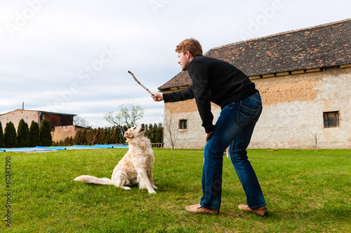 Young man playing with his dog in garden