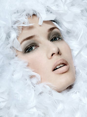 fashionable woman's face surrounded by white feathers