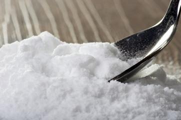 Iron spoon of baking soda close up