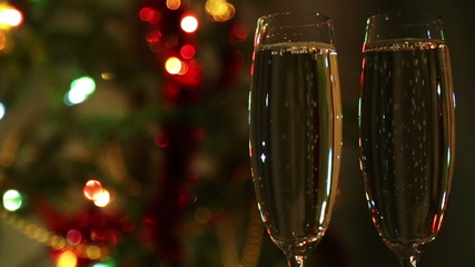glasses with champagne against festive lights background