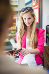 Beautiful young woman paying for her groceries at the counter