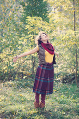 Beautiful smiling woman in bright clothes in the park