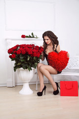 Valentine's Day. Beautiful sexy woman with gift red heart and bo