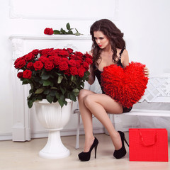 Sexy beautiful woman holding red heart and bouquet of roses . Va