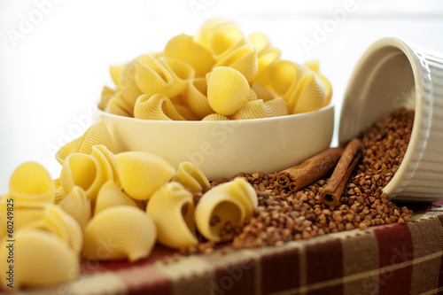 White porcelain plates with dry Snailshell-shaped pasta and buck