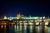 Prague Castle illuminated at night over Charles Bridge