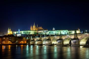 Prague Castle illuminated at night over Charles Bridge