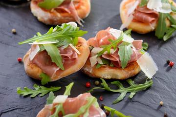 Minipizzen mit Parmaschinken und Rucola auf Schieferplatte
